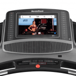 Console screen of the Nordictrack commercial 2450 treadmill with an image of a woman conducting a fitness class. The treadmill features a fan, several buttons, 2 cup holders and a speaker