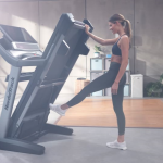 A woman wearing athletic attire folding up the Nordictrack 2950 treadmill in a living room with a bright window, desk, plants and 2 weights on the floor