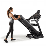A woman in athletic attire folding the Sole F80 Treadmill