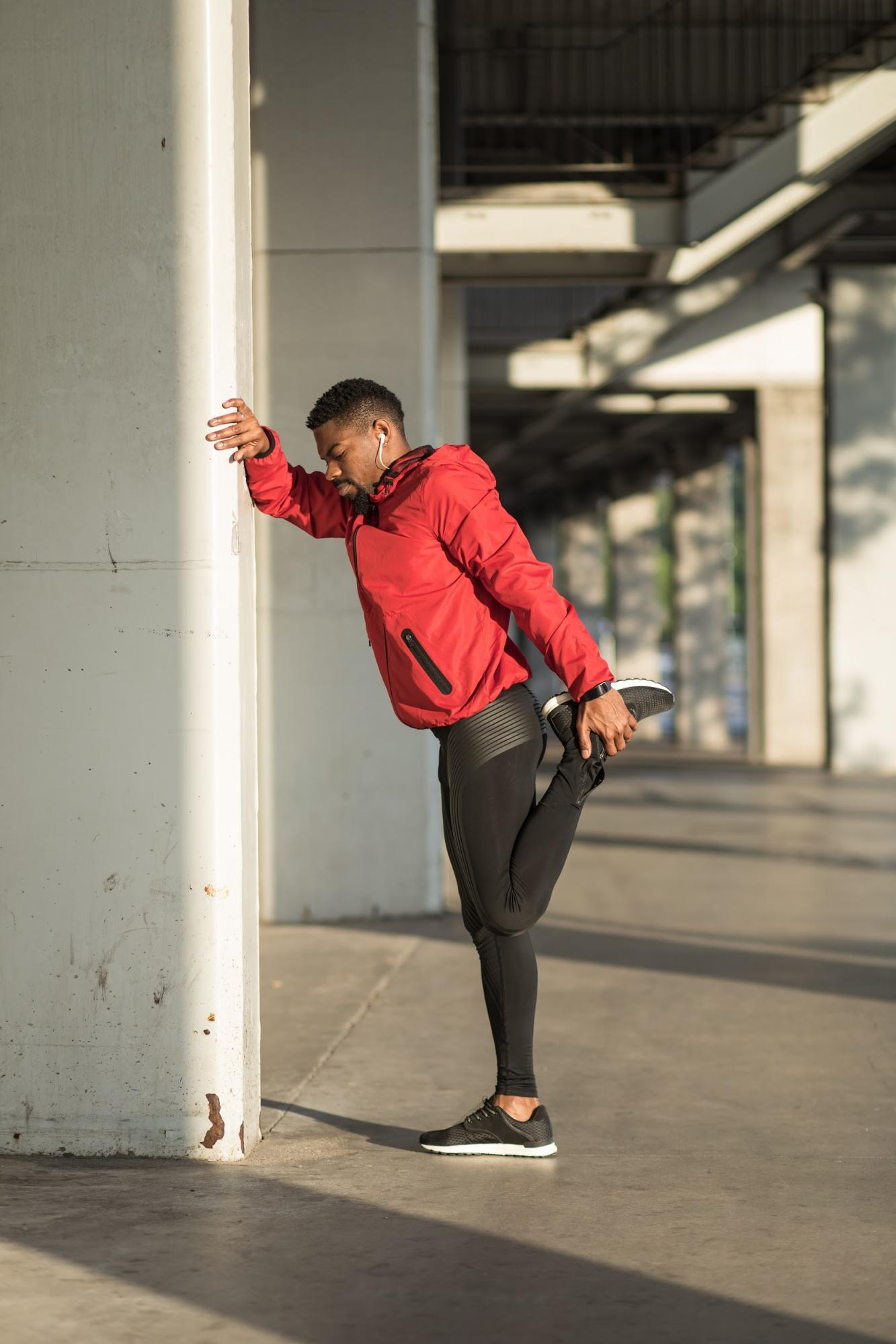 male in red jacket stretching leg against wall