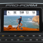 Console screen of the ProForm Pro 9000 treadmill with an image of a man in athletic attire running alongside a mountain with a view of the ocean behind him. The treadmill features a fan, several buttons and a speaker