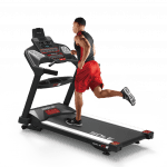 A man in athletic attire running on the Sole TT8 treadmill
