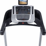 Console of the Nordictrack C 700 Treadmill with a an image of a beach on the tablet. The treadmill includes 2 cup holders, a fan, a speaker, a tablet holder and several buttons
