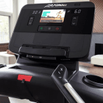 Console of the Life Fitness Club Series Plus Treadmill. This features a digital screen with a woman leading a workout, a tablet holder, a speaker and several buttons