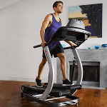 A fit man in athletic attire working out on the Bowflex TC200 TreadClimber in a living room setting