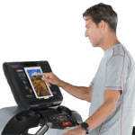 A fit man in athletic attire walking on the Landice L7 Treadmill setting up his workout on the screen