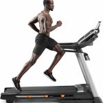 A fit man in athletic attire running on the C 1650 treadmill