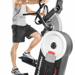 A man in athletic attire working out on the ProForm HIIT Trainer Elliptical