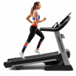 A fit woman in athletic attire running on the treadmill in an upward angle
