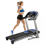 A fit woman in athletic attire running on the Horizon T101 Treadmill